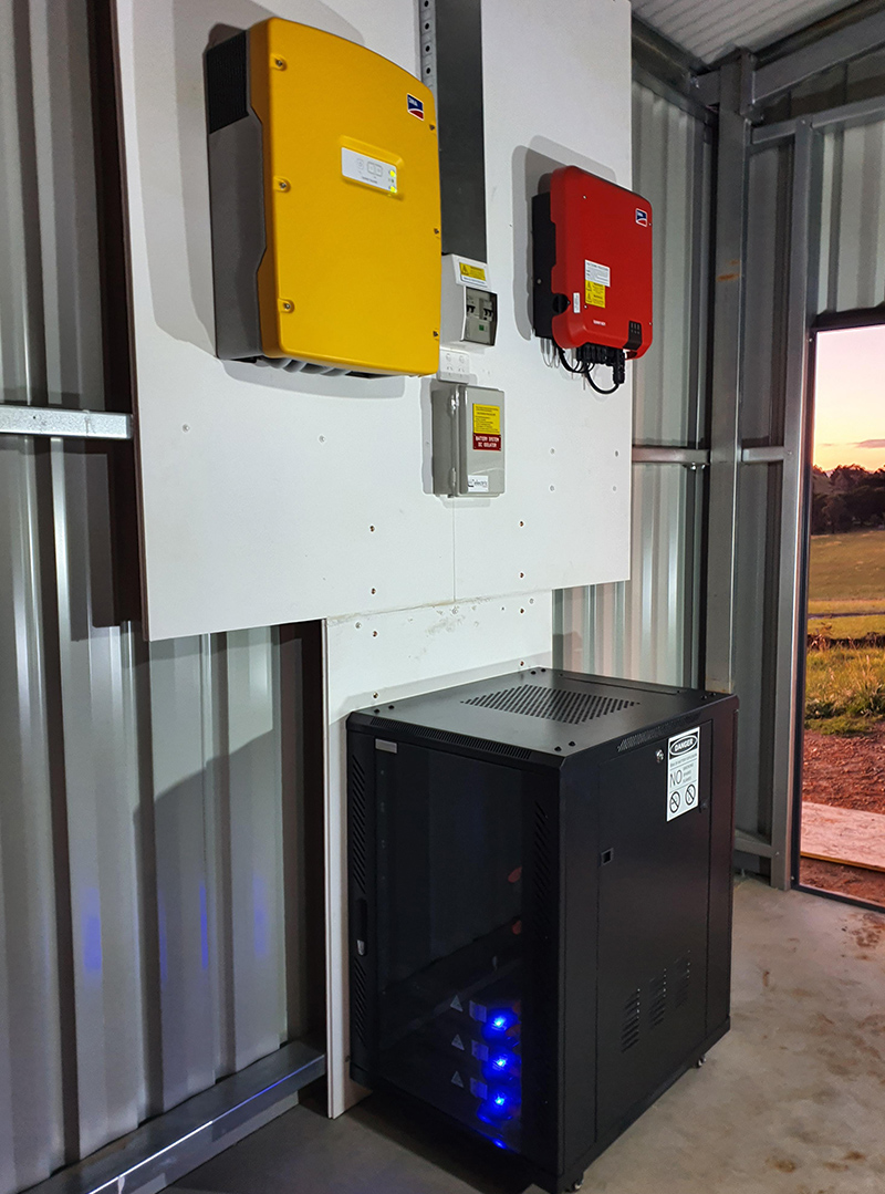 an off grid solar and battery installation on a shed wall